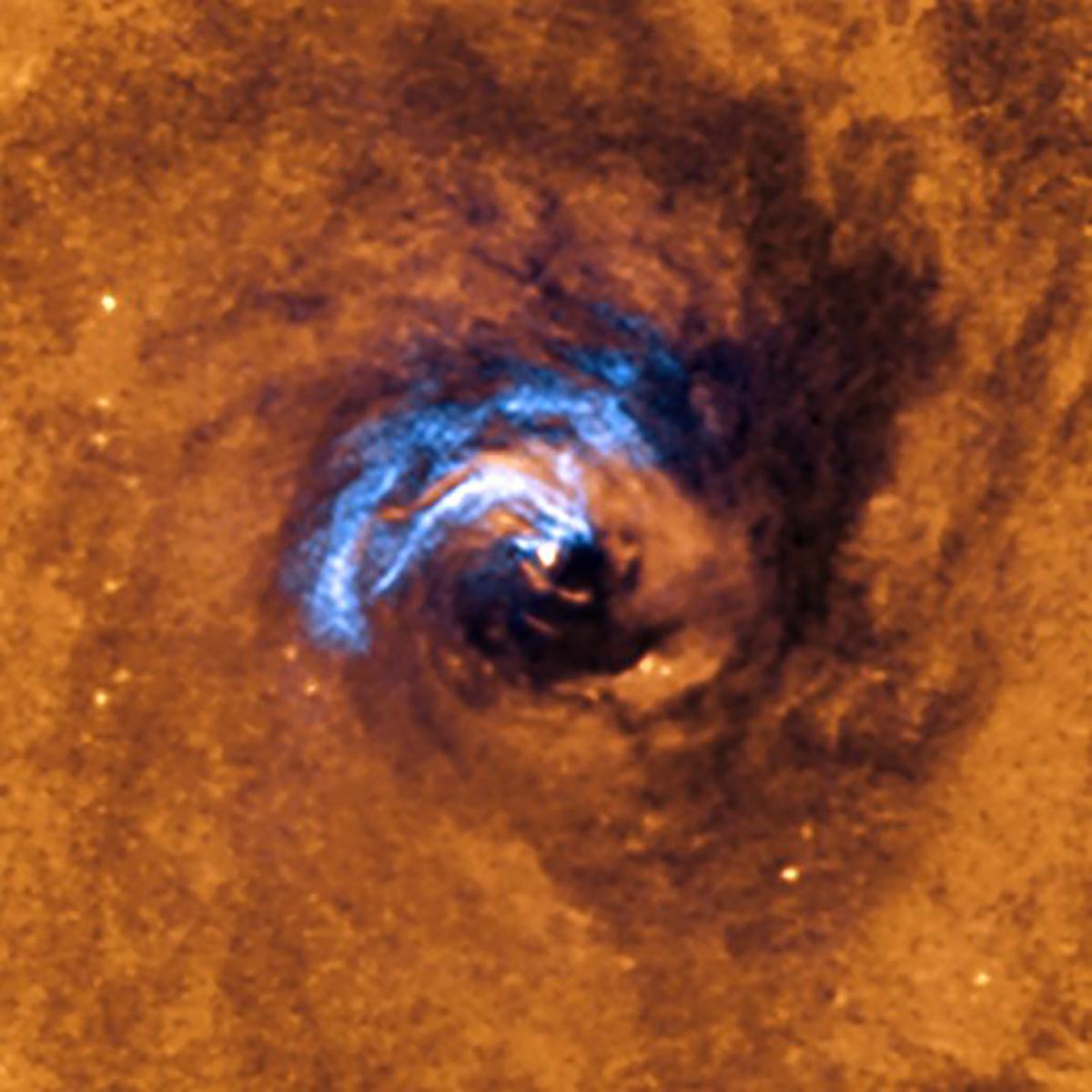 La imagen muestra el proceso de alimentación nuclear de un agujero negro en la galaxia NGC 1566 y cómo los filamentos de polvo que envuelven el núcleo activo quedan atrapados y giran en espiral alrededor del agujero negro hasta que son tragados por él.